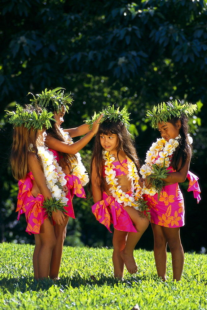 Four Keiki Hula Girls In Colorful Pareos With Haku And Leis Fix Each Other B1402