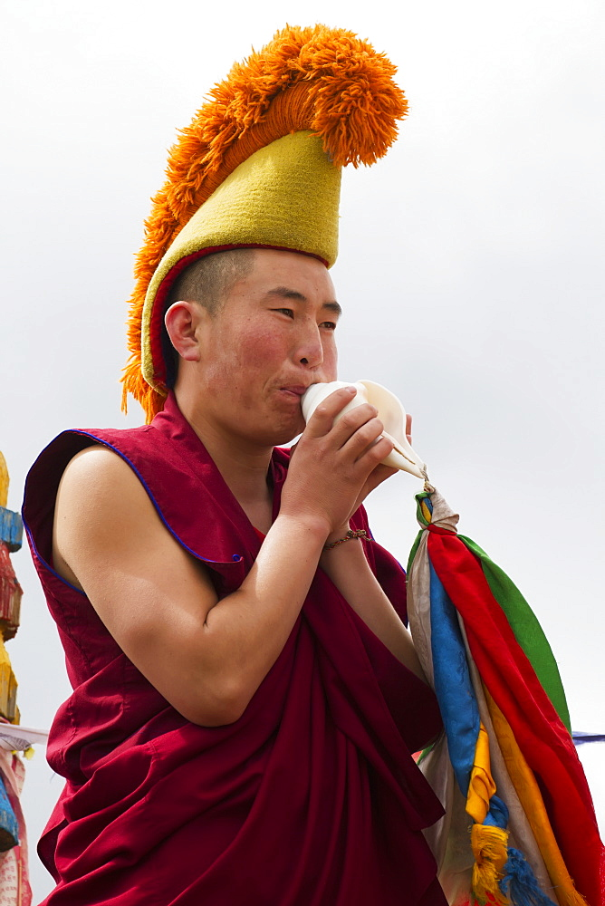 Buddhist monk blowing a conch shell by the Larviran Temple at the Erdene Zuu Monastery, Karakorum (Kharkhorin), Övörkhangai Province, Mongolia
