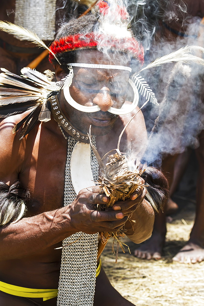 Dani men wearing an elaborate headdress of bird of paradise or cassowary feathers lighting a fire, Obia Village, Baliem Valley, Central Highlands of Western New Guinea, Papua, Indonesia