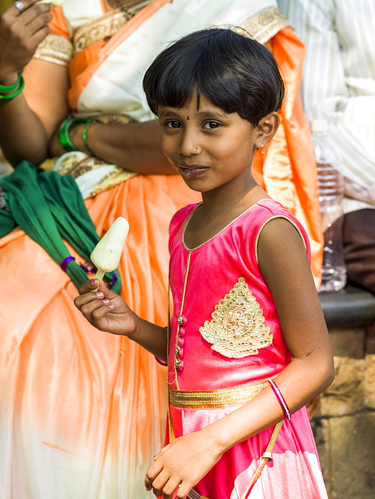 A young girl in a bright pink dress eating a popsicle and smiling for the camera, Mumbai, Maharashtra, India - 1116-39779