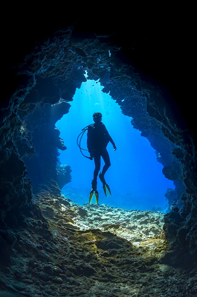 Diver at one of the many openings around the dive site called First Cathedral off the island of Lanai, Hawaii, United States of America