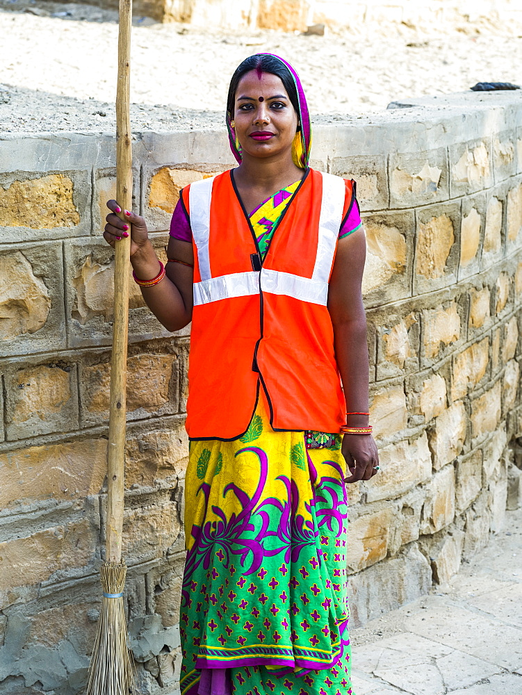 Portrait of an Indian woman wearing a reflective vest and holding a broom, Jaisalmer, Rajasthan, India