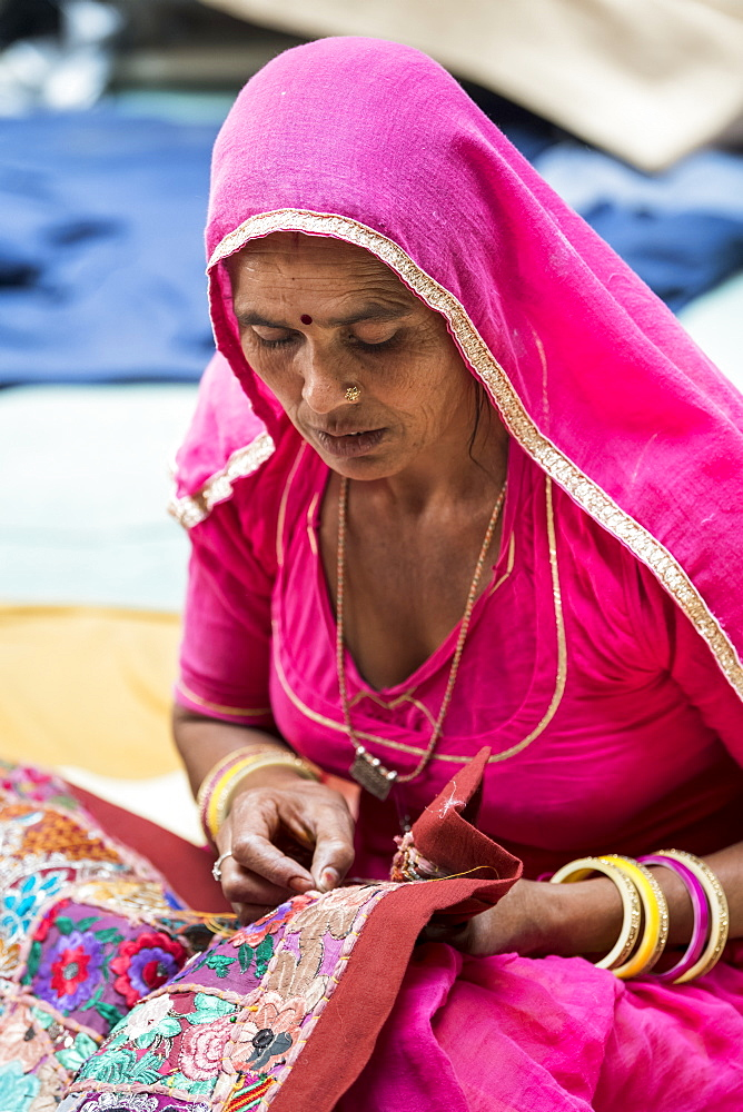 A Hindu Indian woman sits doing needlework, Fort Jaisalmer, Jaisalmer, Rajasthan, India