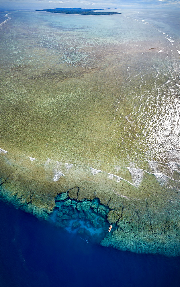 Aerial view of the southern end of the reef surrounding the island of Yap, with a dive boat anchored at Yap Caverns, a famous site for scuba divers, Ngariy, Yap, Micronesia