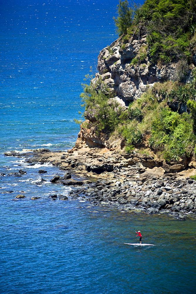 Woman paddling out from Maliko Gulch on stand up paddle board, near Paia, Maui, Hawaii, United States of America