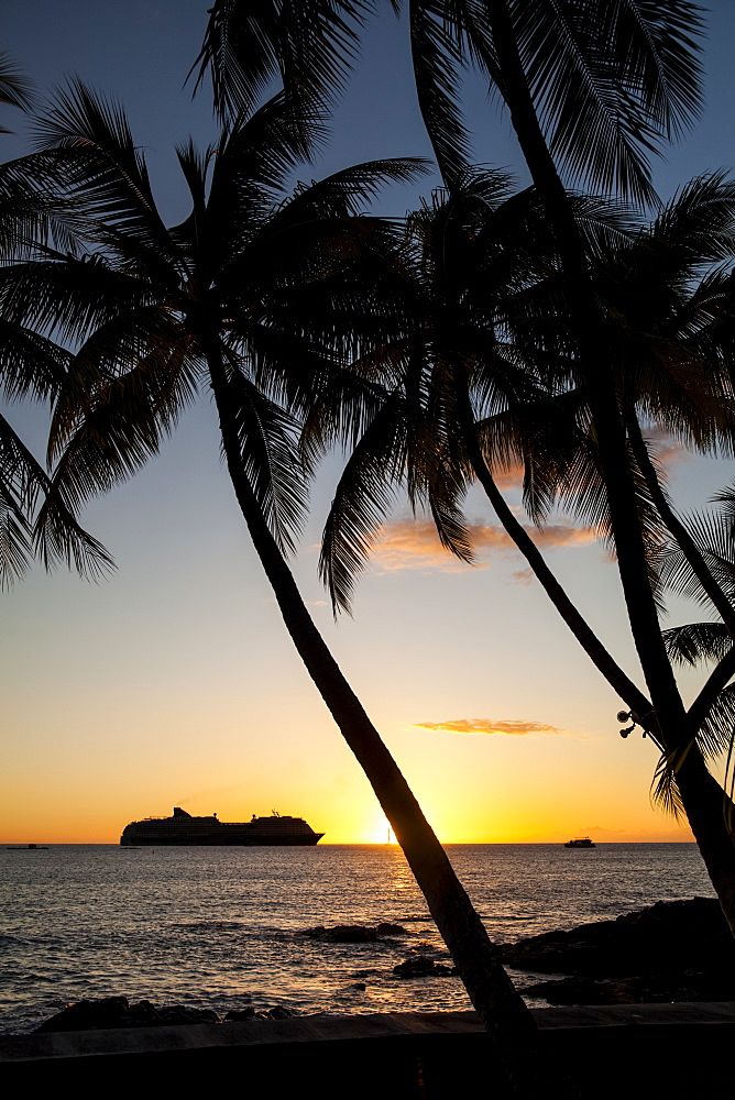 Silhouette of a cruise ship on the water off the shore of Kailua Bay at sunset, Kailua-Kona, Island of Hawaii, Hawaii, United States of America