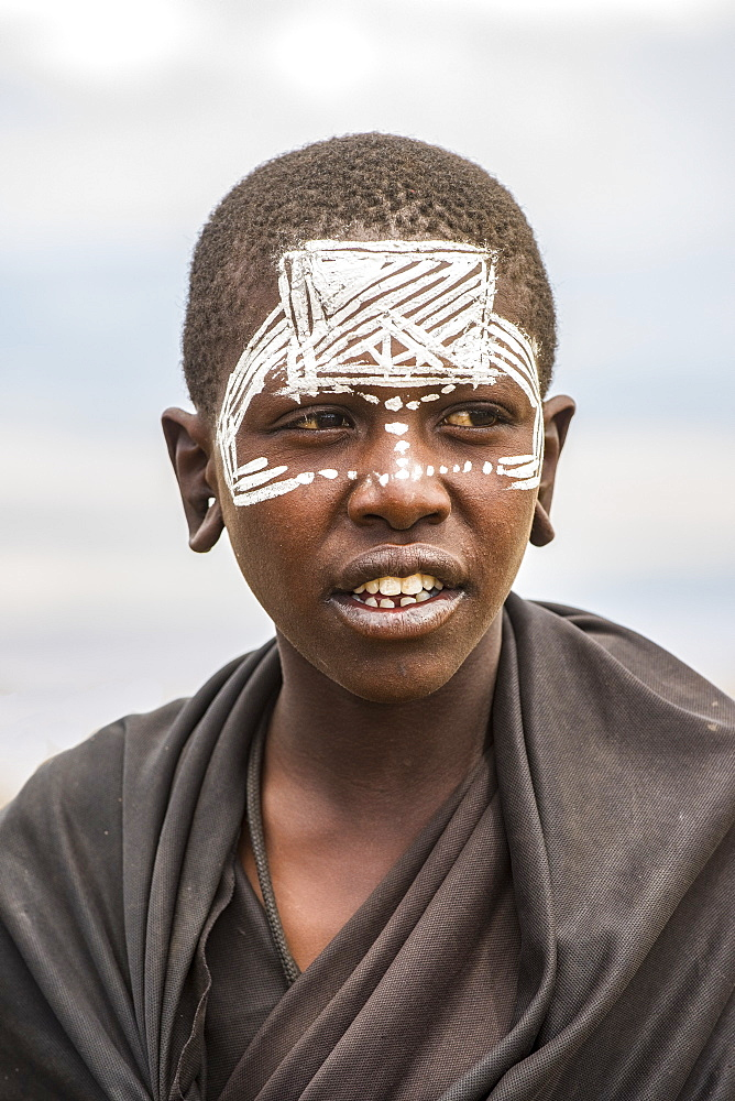 Maasai youth with traditional face paint signifying that he has completed the initiation process for entering adulthood the Ngorongoro Conservation Area, Tanzania