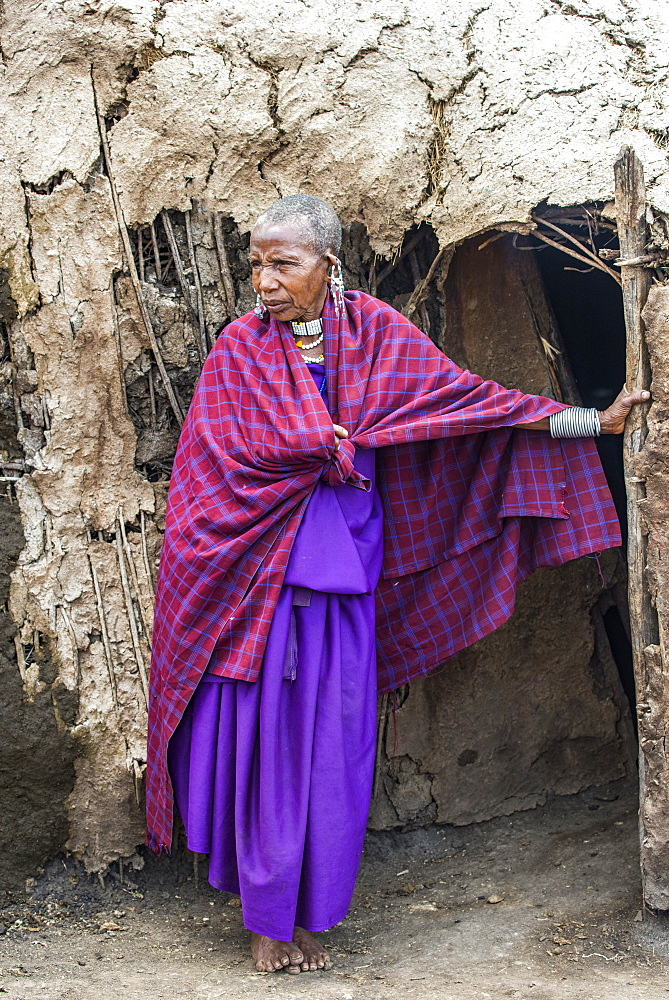 Maasai woman elder wearing traditional clothing stands at entrance to her mud hut in the Ngorongoro Conservation Area, Tanzania