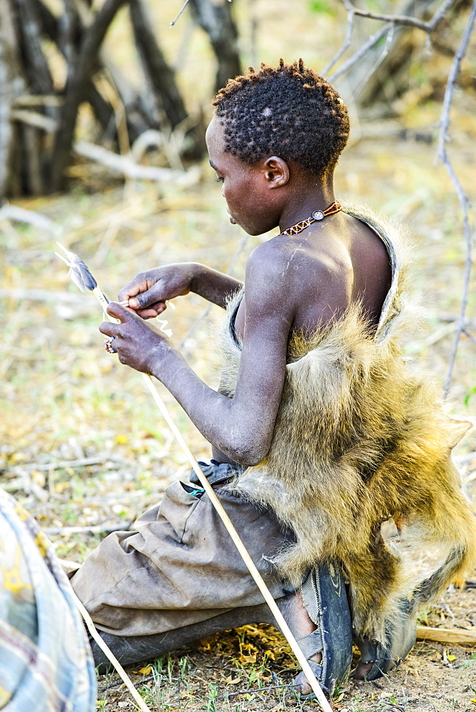 Young Hadzabe hunter wearing baboon skin cloak fletches arrow with feathers from a bird shot earlier in the morning near Lake Eyasi, Tanzania