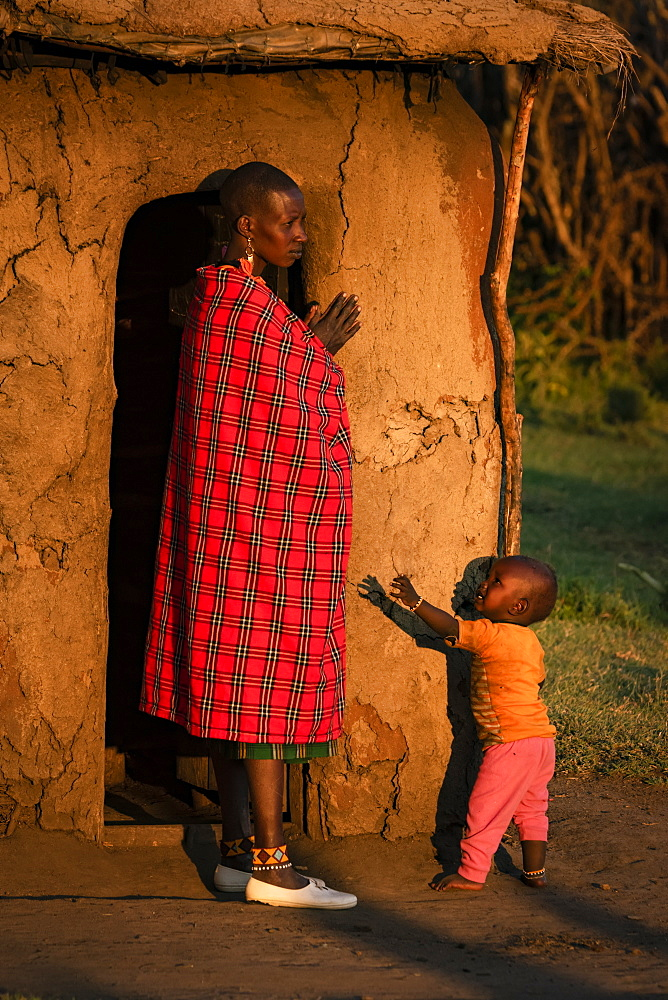 Woman in shuka with child outside hut, Tanzania