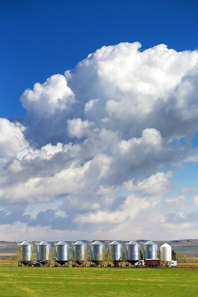 A row of large metal grain bins with dramatic storm clouds and blue sky in the background, West of Calgary, Alberta, Canada