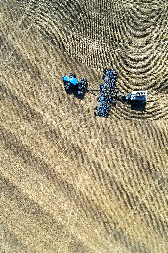 Aerial view of air seeder in field, near Beiseker, Alberta, Canada