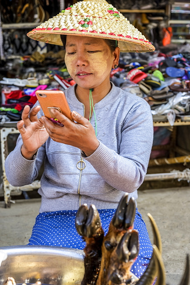 Woman on her smartphone at the market, Lashio, Shan State, Myanmar