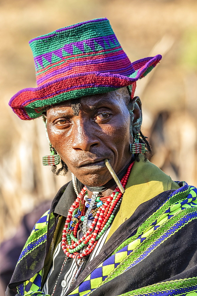 Hamer man wearing a colourful hat at a bull jumping ceremony, which initiates a boy into manhood, in the village of Asile, Omo Valley, Ethiopia