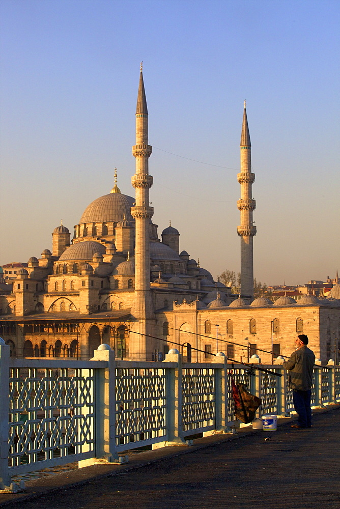 Fisherman on Galata Bridge with New Mosque in background, Istanbul, Turkey, Europe