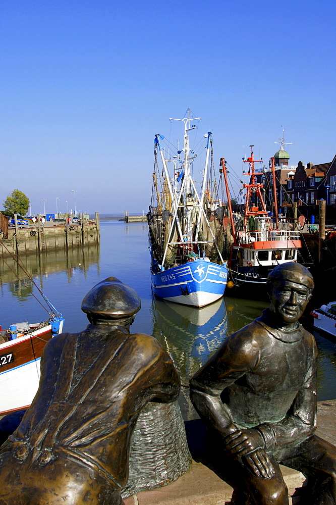 Sculpures and shrimps cutter in harbour, Neuharlingersiel, Lower Saxony, Germany