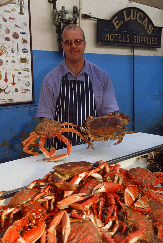 Vendor selling Crabs at market stall, St. Peter Port, Guernsey, Channel Islands, Great Britain