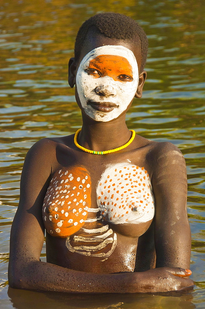 Young Surma woman with body paintings in river, Kibish, Omo River Valley, Ethiopia