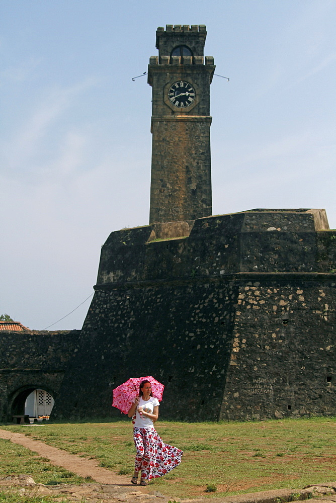Lady with pink parasol at Clock Tower, Galle, Sri Lanka, Asia