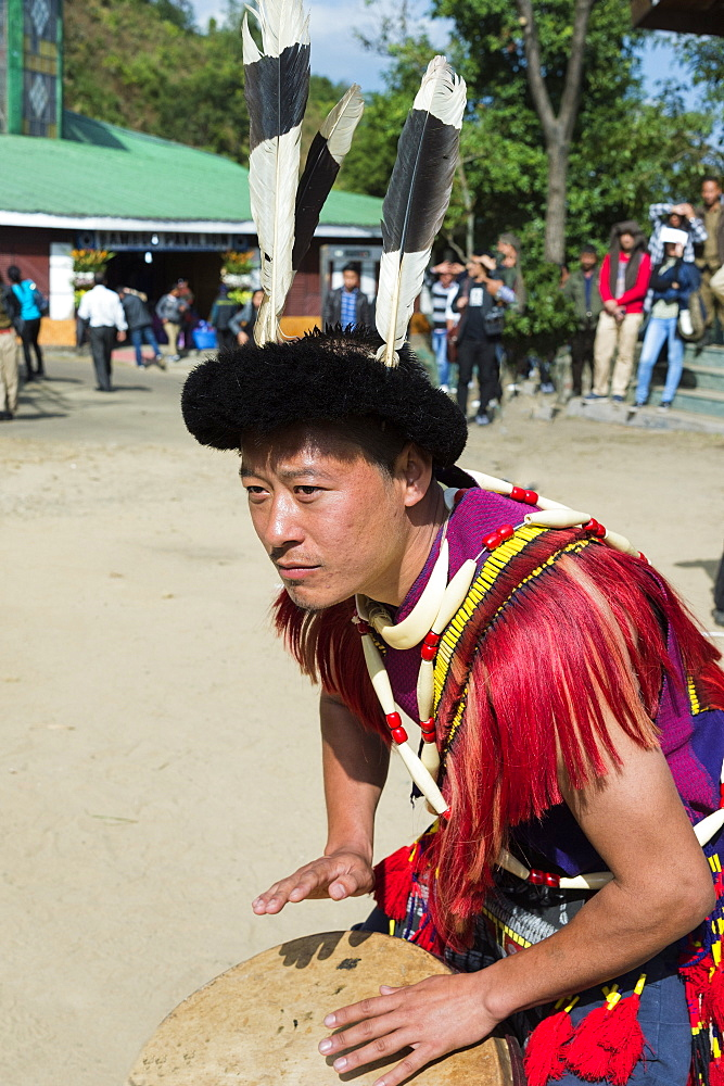 Naga tribal man in traditional outfit playing drum, Kisima Nagaland Hornbill festival, Kohima, Nagaland, India, Asia - 1131-1021