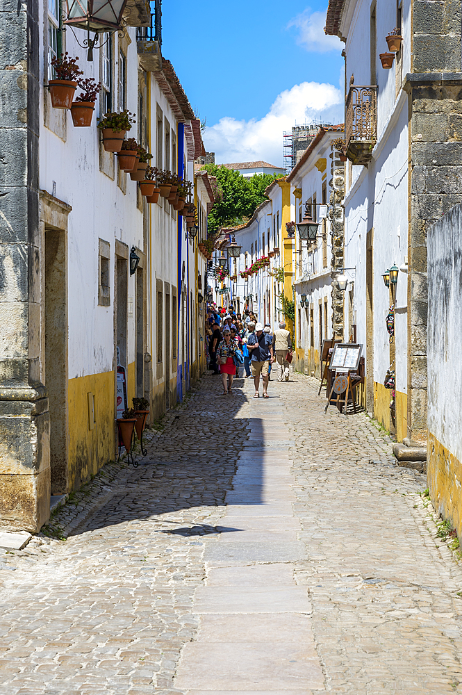 Typical narrow street with shops and tourists in the fortified city of Obidos, Leiria District, Estremadura, Portugal, Europe
