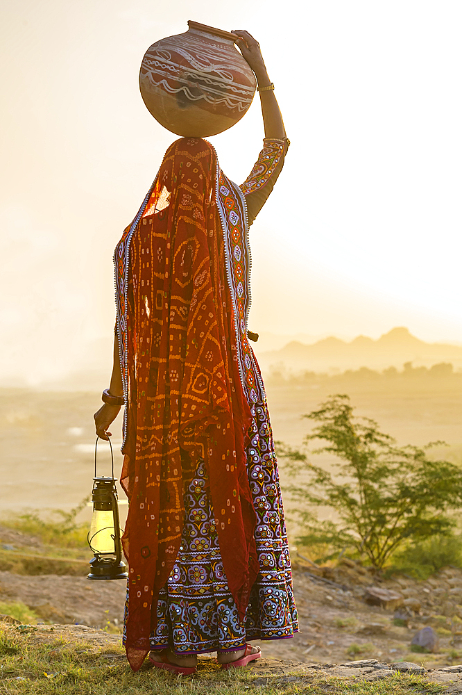 Ahir Woman in traditional colorful cloth carrying water in a clay jug on her head, Great Rann of Kutch Desert, Gujarat, India