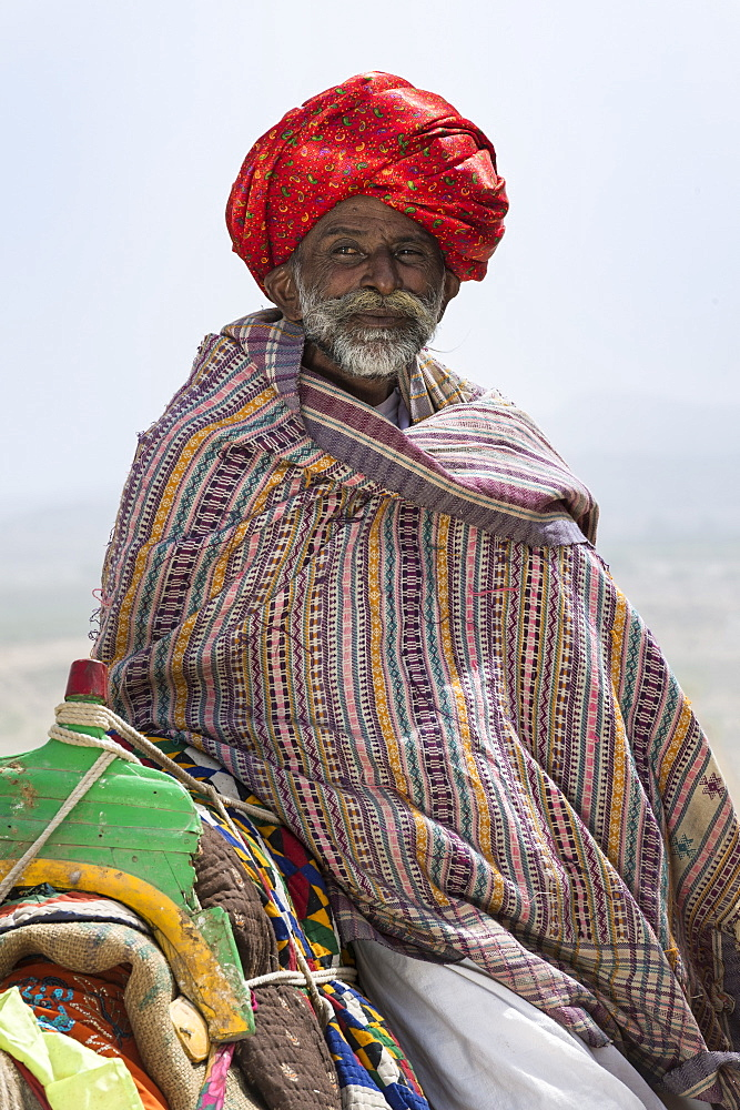 Man of the Dhebariya Rabari community in traditional cloth with a dromedary, Great Rann of Kutch Desert, Gujarat, India, Asia - 1131-1253