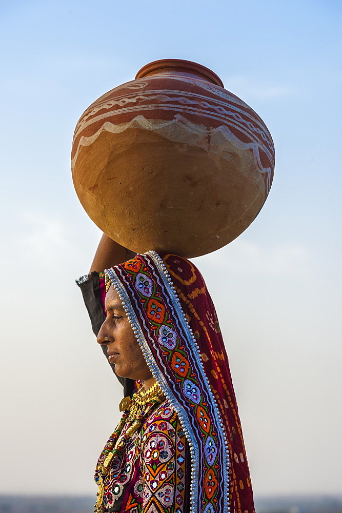 Ahir Woman in traditional colorful cloth carrying water in a clay jug on her head, Great Rann of Kutch Desert, Gujarat, India, Asia - 1131-1254