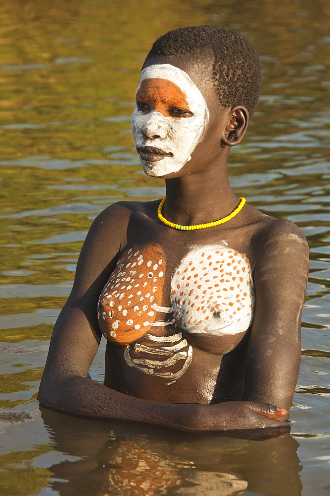 Young Surma woman with body paintings in the river, Kibish, Omo River Valley, Ethiopia, Africa
