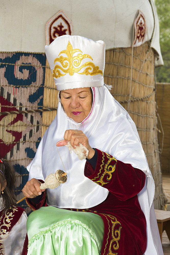 Kazakh woman spinning wool, Kazakh ethnographical village Aul Gunny, Talgar city, Almaty, Kazakhstan, Central Asia, Asia