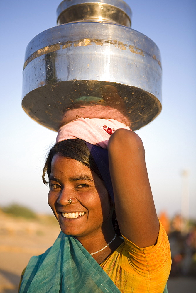 Young woman collecting water, Jaisalmer, Western Rajasthan, India, Asia
