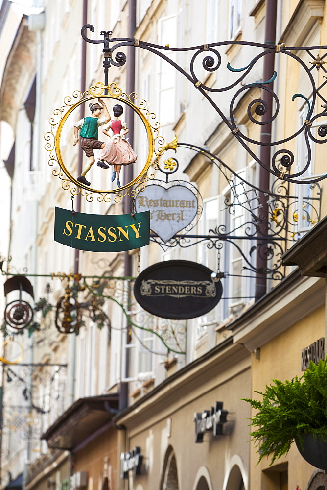 Ornate shop signs on Getreidegasse, Salzburgs bustling shopping street, Salzburg, Salzburger Land, Austria, Europe