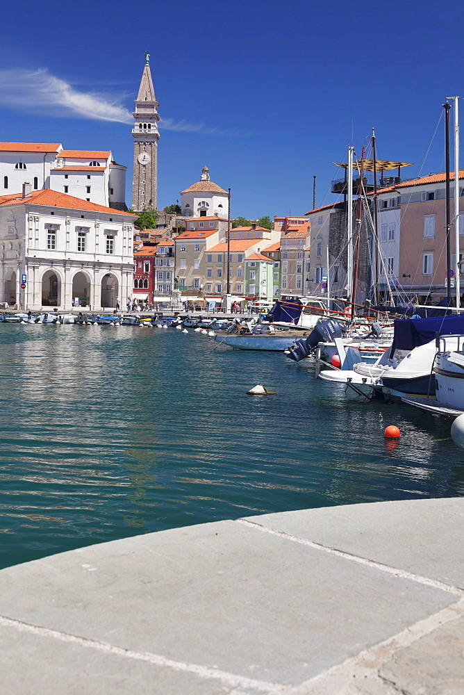 Waterfront buildings at the harbour and bell tower of Cathedral of St. George, Piran, Istria, Slovenia, Europe
