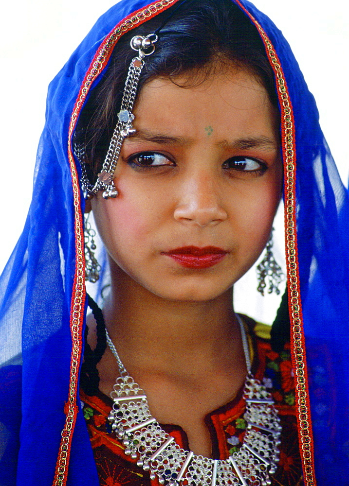 A young girl in traditional costume with silver filigree necklace and earrings and a brightly coloured veil, Pakistan - 1161-1167