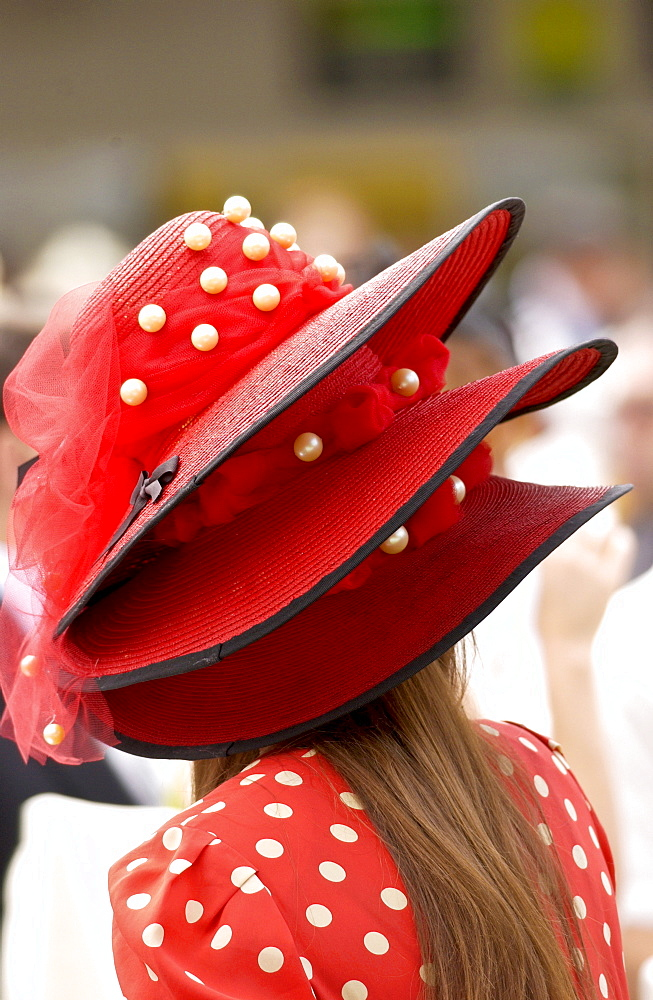 Race-goer in true Ascot fashion wearing a matching spotted dress and three tiered hat at Royal Ascot Races
