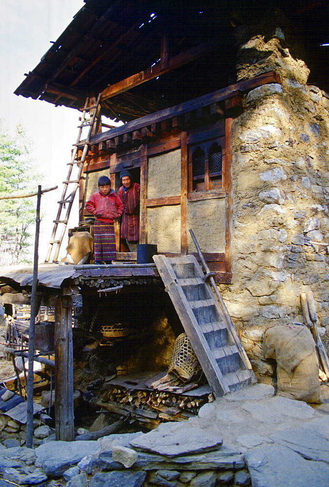 Father and son stand in doorway of their home in Paro, Bhutan