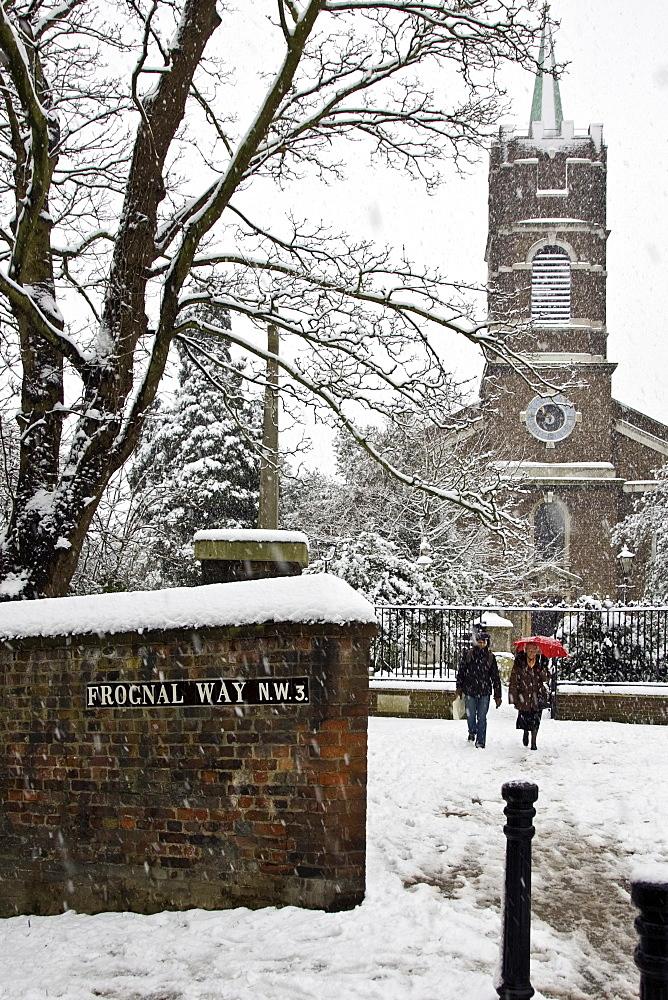 Two people walk by St John At Hampstead Parish Church and graveyard, North London, UK