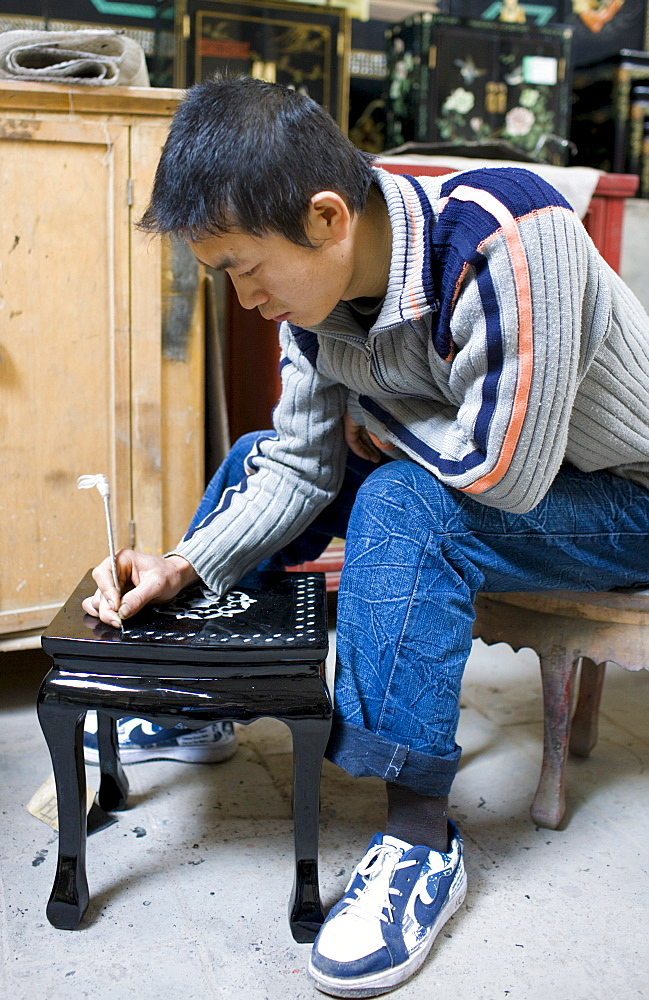 Marquetry craftsman at work on lacquer table at souvenir and furniture factory, Xian, China