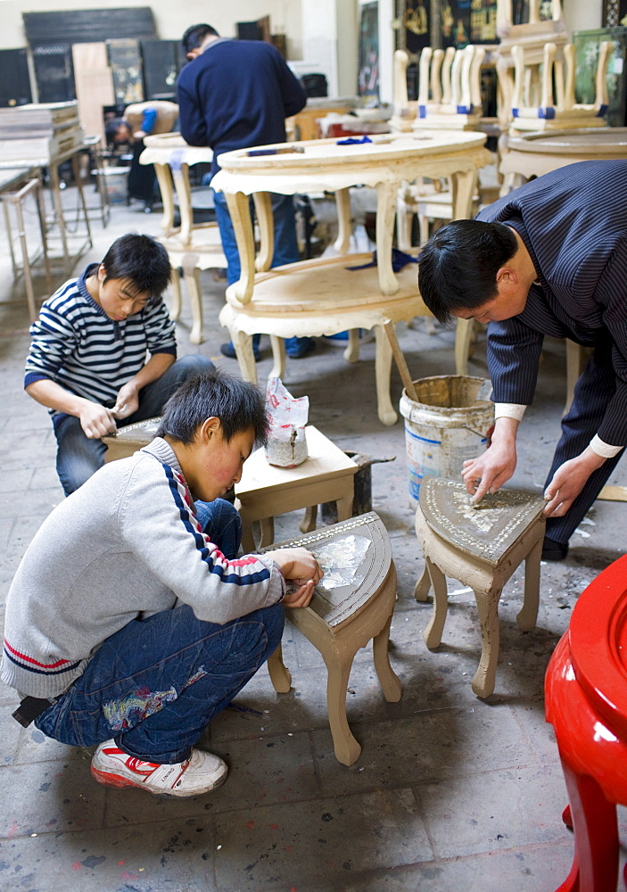 Marquetry craftsmen at work on lacquer tables at souvenir and furniture factory, Xian, China