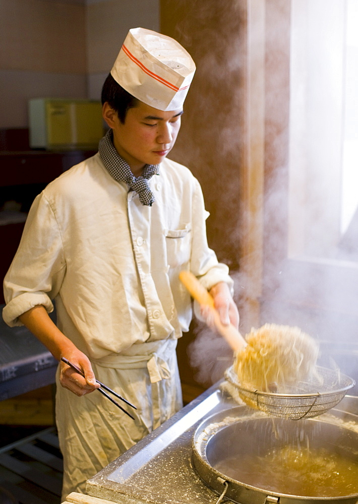 Chef cooking noodles in tourist restaurant, Xian, China