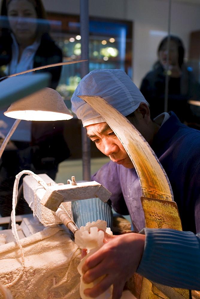 Jade craftsman at work in the Beijing Dragon Land factory in Beijing, China