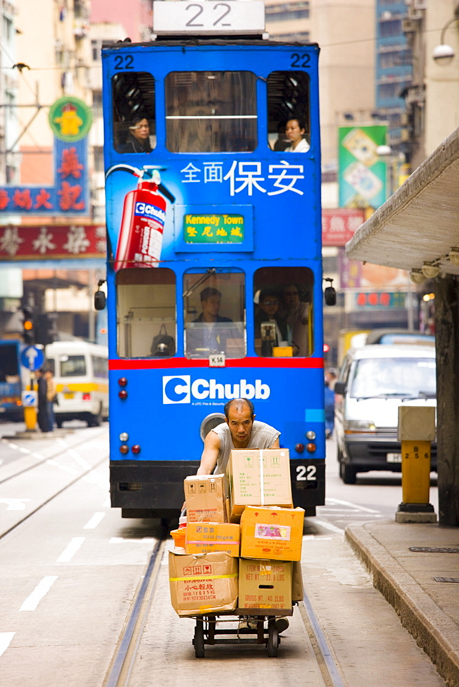 Tram behind man delivering food by trolley in old Chinese district, Des Voeux Road, Sheung Wan, Hong Kong, China