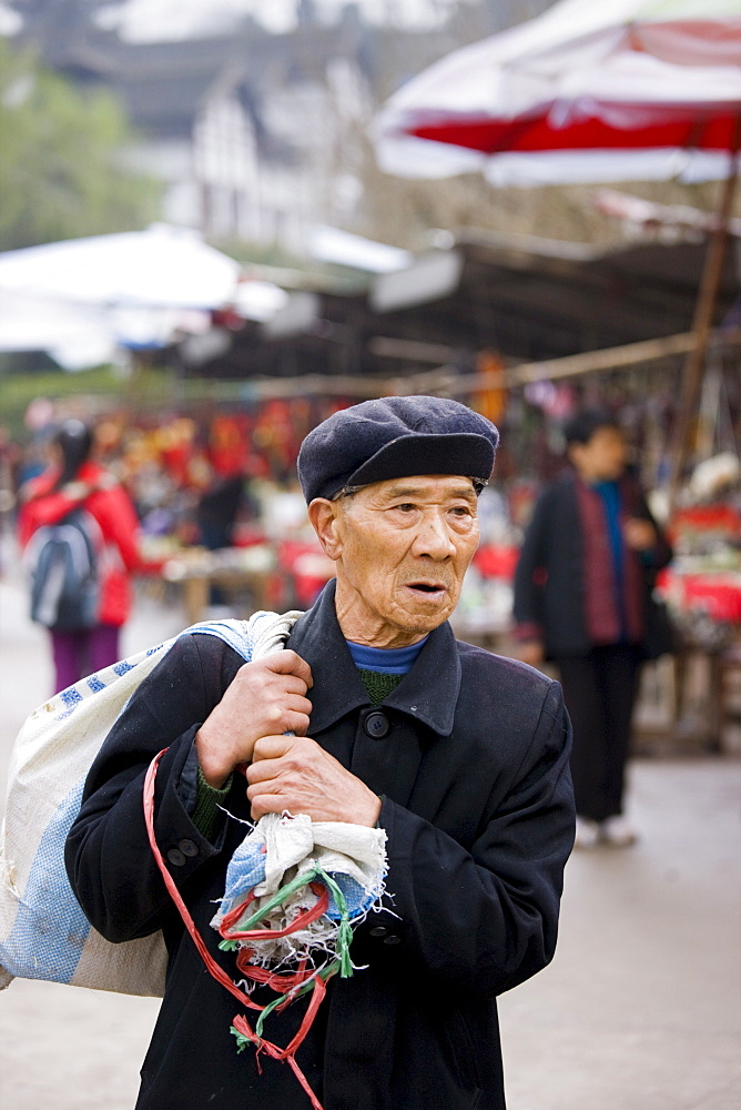 Elderly Chinese man carrying sack through Chongqing, China