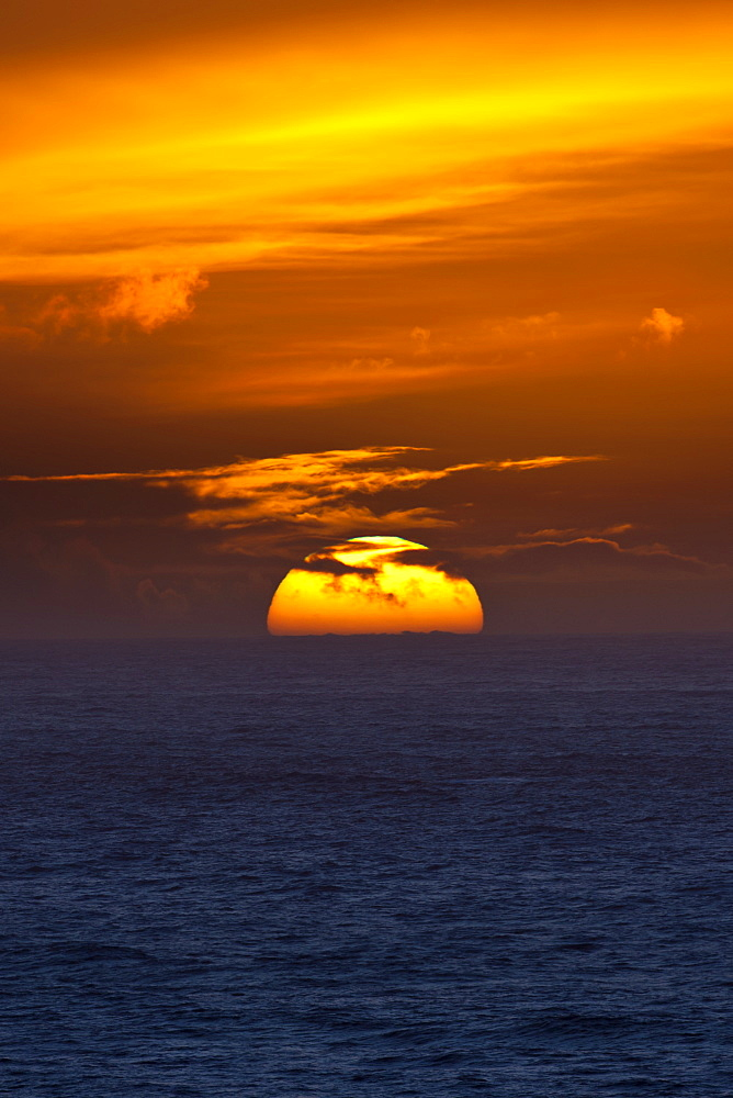Sun setting in the west over the ocean at Woolacombe, North Devon, UK