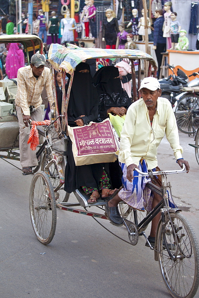Muslim women travel by rickshaw in crowded street scene in city of Varanasi, Benares, Northern India