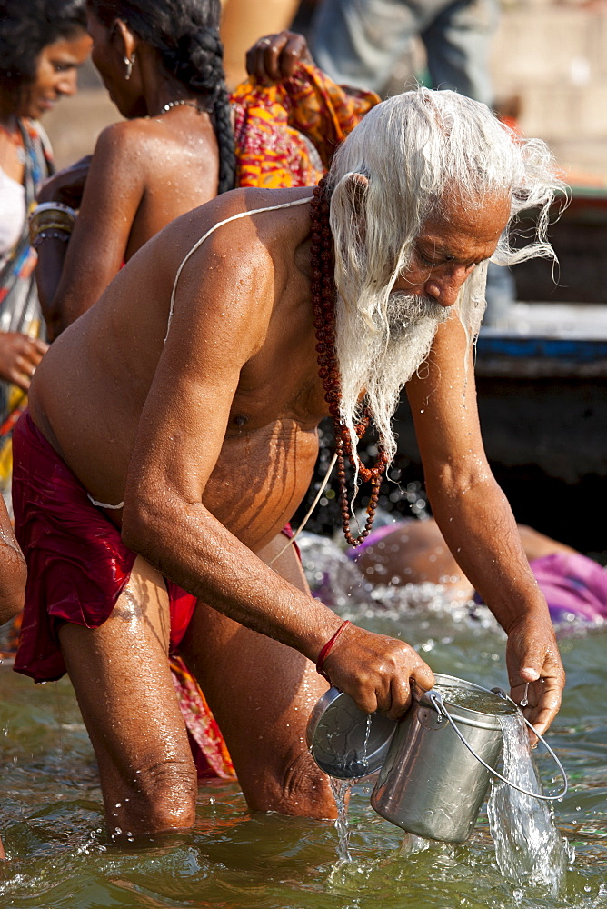 Indian Hindu pilgrim bathing in The Ganges River at Dashashwamedh Ghat in Holy City of Varanasi, Benares, India