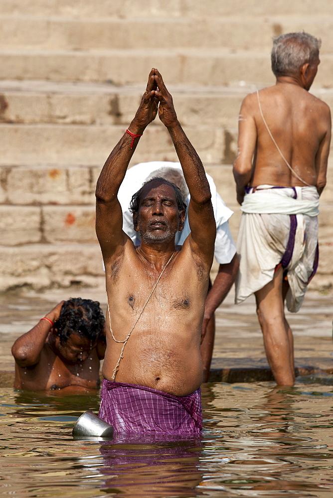 Indian Hindu man bathing and praying in the River Ganges by Kshameshwar Ghat in holy city of Varanasi, India - 1161-4541