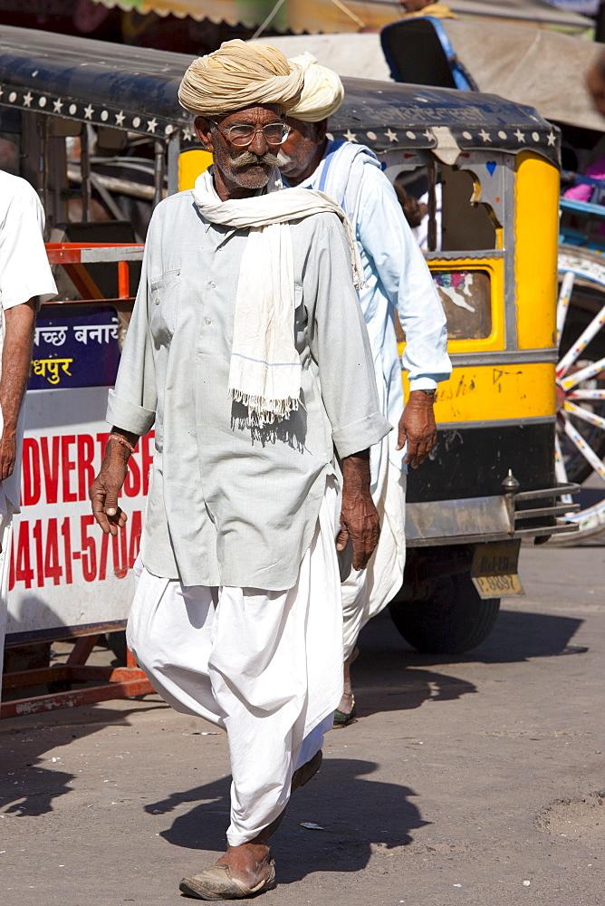 Indian man in traditional dhoti trousers and turban at Sardar Market at Girdikot, Jodhpur, Rajasthan, Northern India