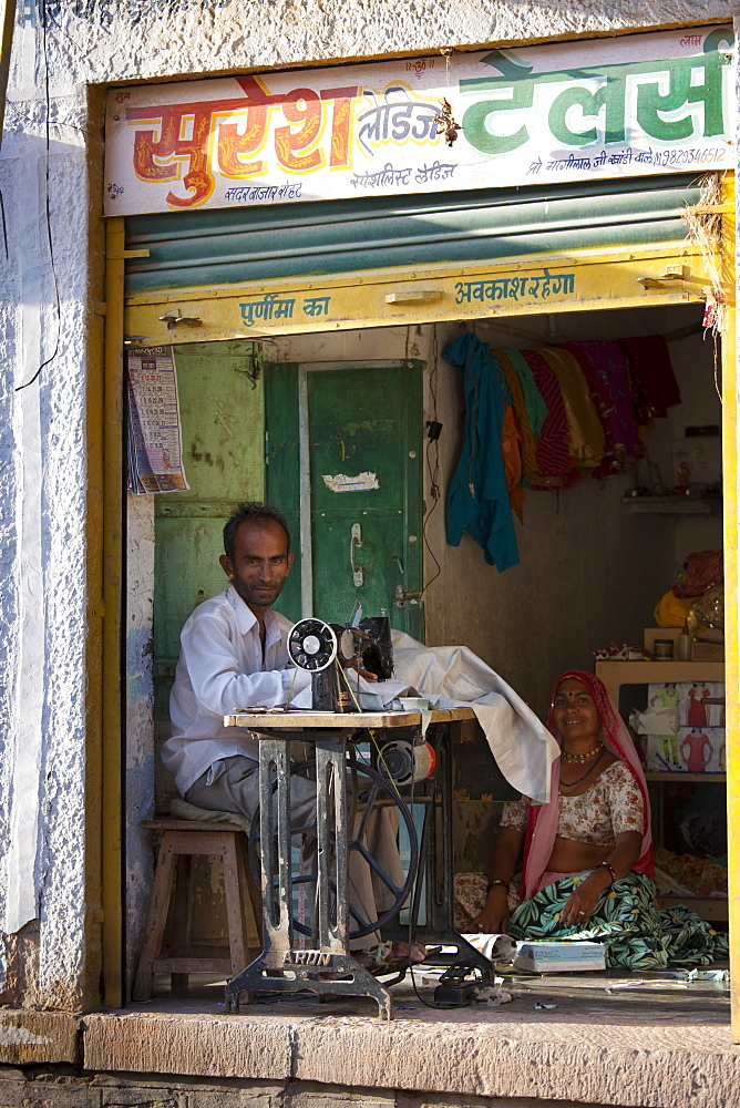 Indian man and wife sewing fabric in village of Rohet in Rajasthan, Northern India - 1161-5112