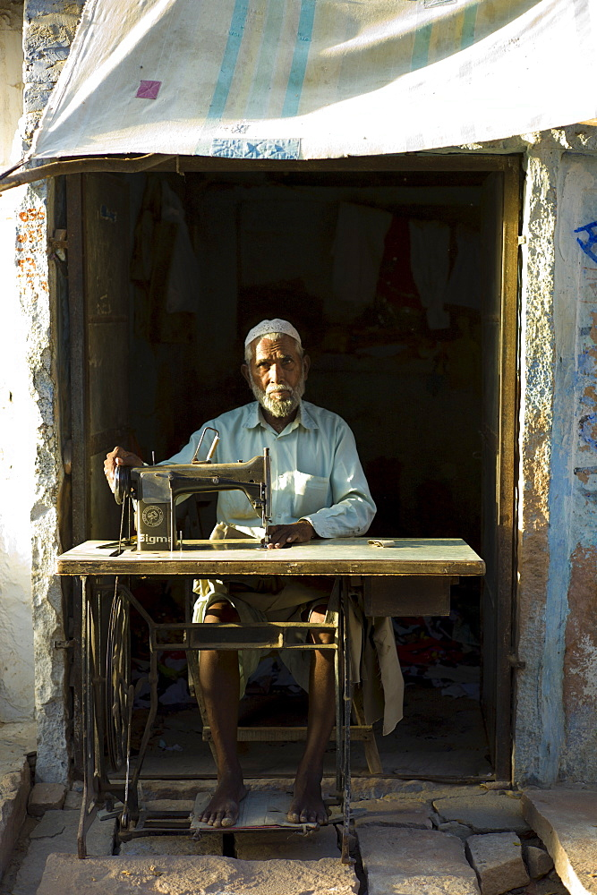 Indian man with sewing machine in village of Rohet in Rajasthan, Northern India